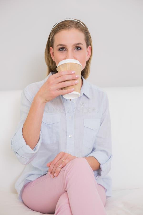 在喝从一次性杯子的长沙发的美满的偶然白肤金发的开会 库存照片