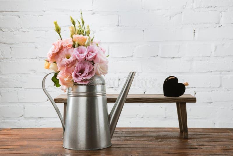 在喷壶和小长凳的嫩花与心脏标志安排了木表面上 库存图片