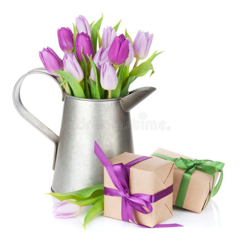 在喷壶和礼物盒的紫色郁金香花束 图库摄影
