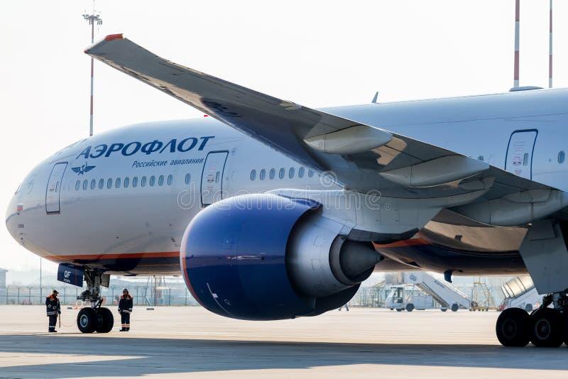 在喷气式客机飞机波音苏航航空公司777-300ER引擎和驾驶舱的看法  两名工作者检查飞机的底盘 免版税库存照片