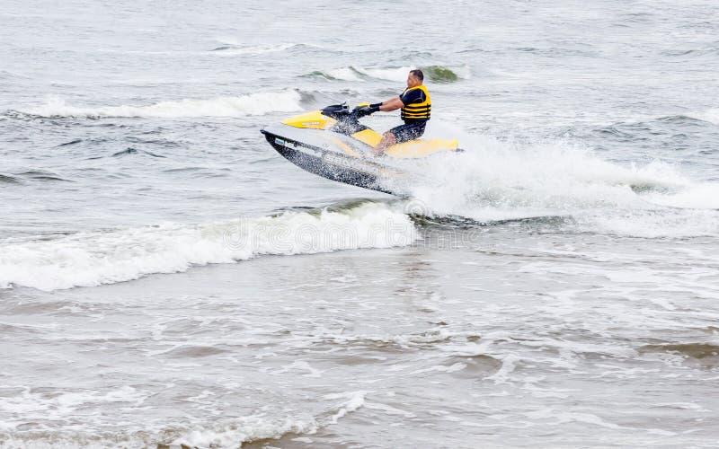 在喷气机滑雪的年轻人骑马在波浪 免版税库存图片