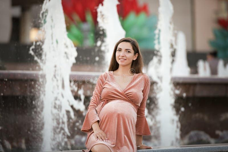 在喷泉附近的怀孕的女孩 愉快和无忧无虑的怀孕 库存照片