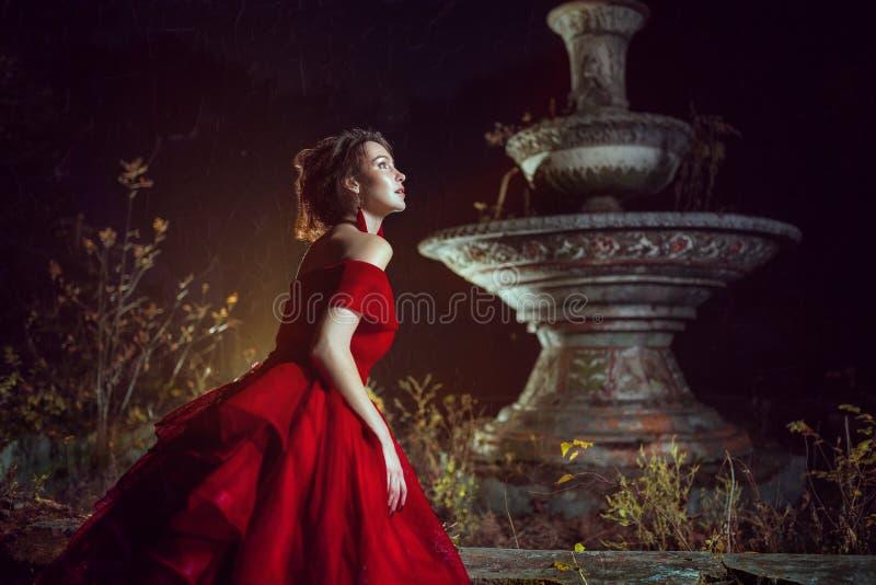 在喷泉附近的美丽的夫人 免版税库存照片