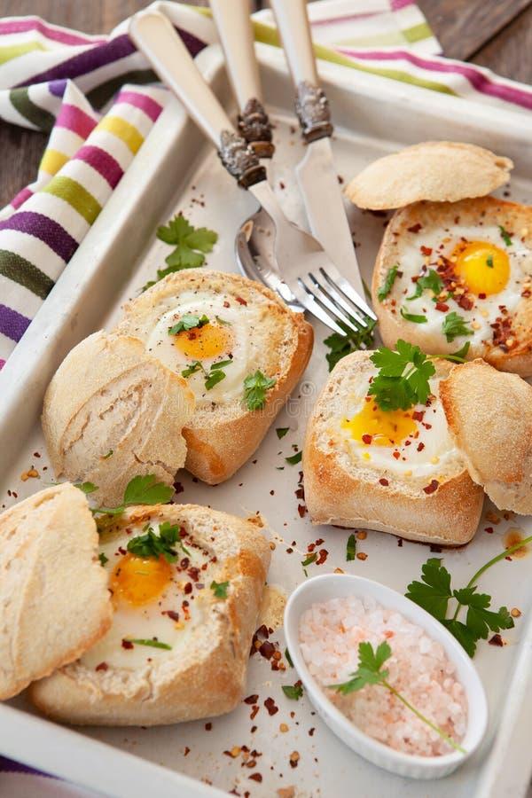 在嘎吱咬嚼的小圆面包的鸡蛋 库存图片