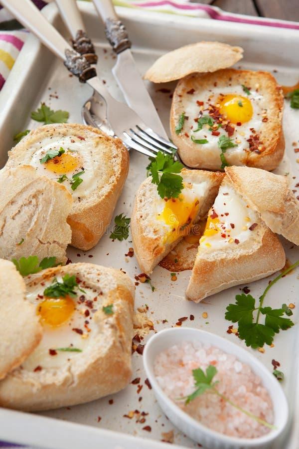 在嘎吱咬嚼的小圆面包的鸡蛋 库存照片