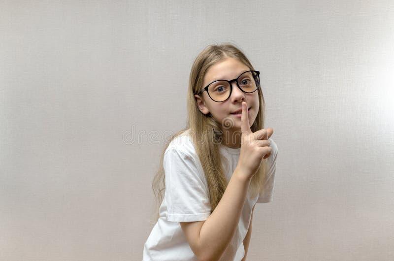 在嘴唇附近的美丽的白肤金发的女孩藏品手指 安静和嘘姿态 r 图库摄影