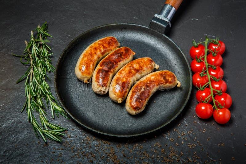 在四个油煎的香肠的顶视图在黑圆的平底锅 图库摄影