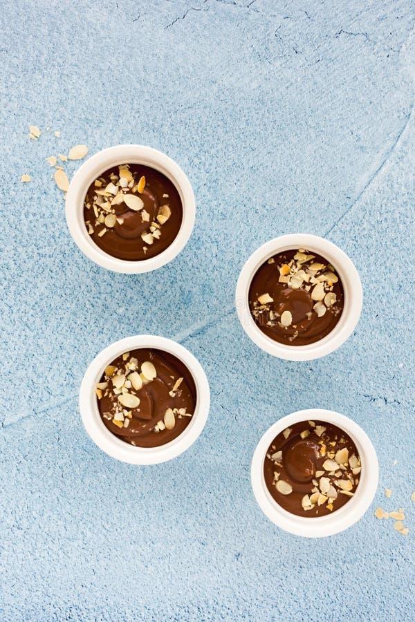 在四个白色陶瓷小模子的自创巧克力布丁,装饰用烤杏仁裂片,在浅兰的混凝土 免版税图库摄影