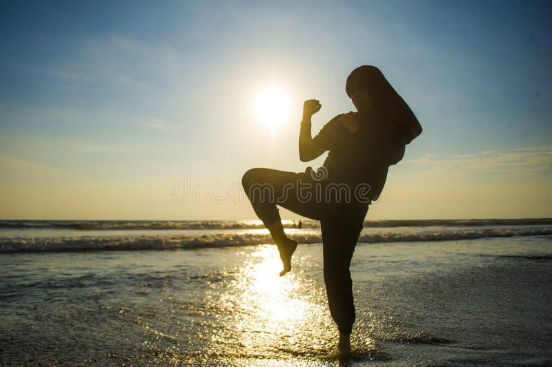 在回教hijab头围巾训练武道空手道反撞力攻击和健身盖的年轻适合的回教妇女剪影  免版税库存照片