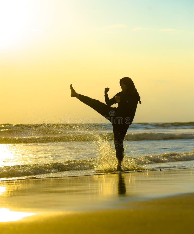 在回教hijab头围巾训练武道空手道反撞力攻击和健身盖的年轻适合的回教妇女剪影  库存照片