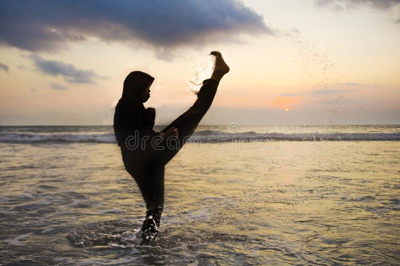 在回教hijab头围巾训练武道空手道反撞力攻击和健身盖的年轻适合的回教妇女剪影  免版税库存图片