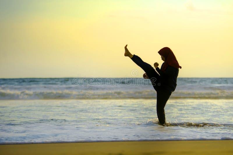 在回教hijab头围巾训练武道空手道反撞力攻击和健身盖的年轻适合的回教妇女剪影  图库摄影