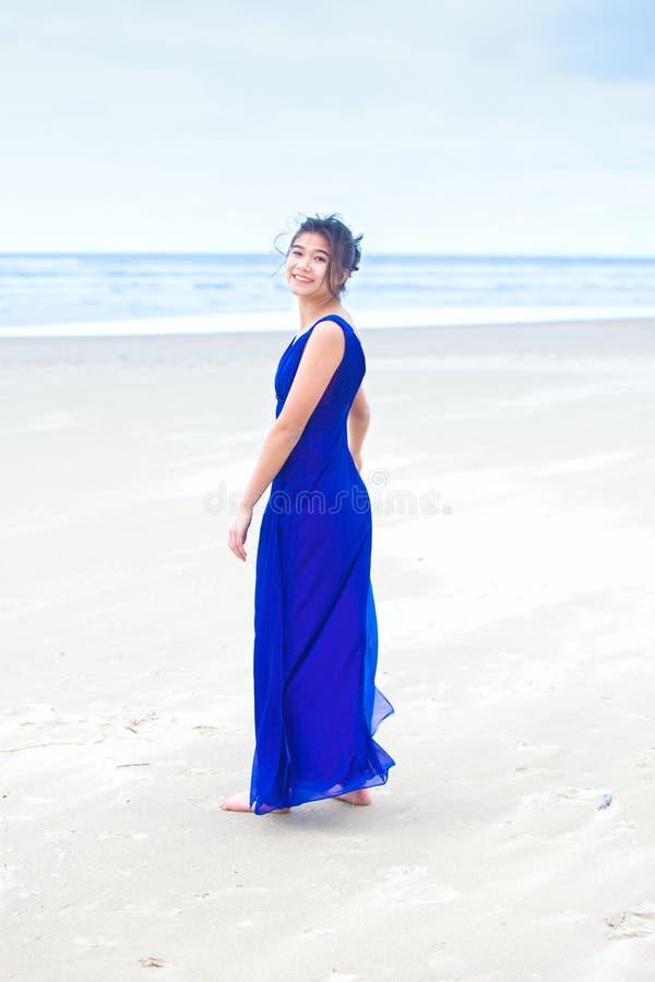 在回顾在肩膀的海滩的青少年的佩带的蓝色礼服 免版税库存图片