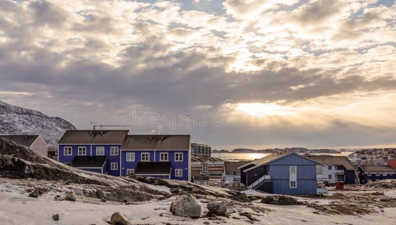 在因纽特人房子的极性日落与雪,努克市,格陵兰的岩石小山的 免版税图库摄影