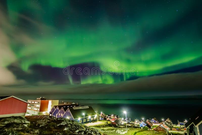 在因纽特人的云彩掩藏的绿色明亮的北极光 库存图片