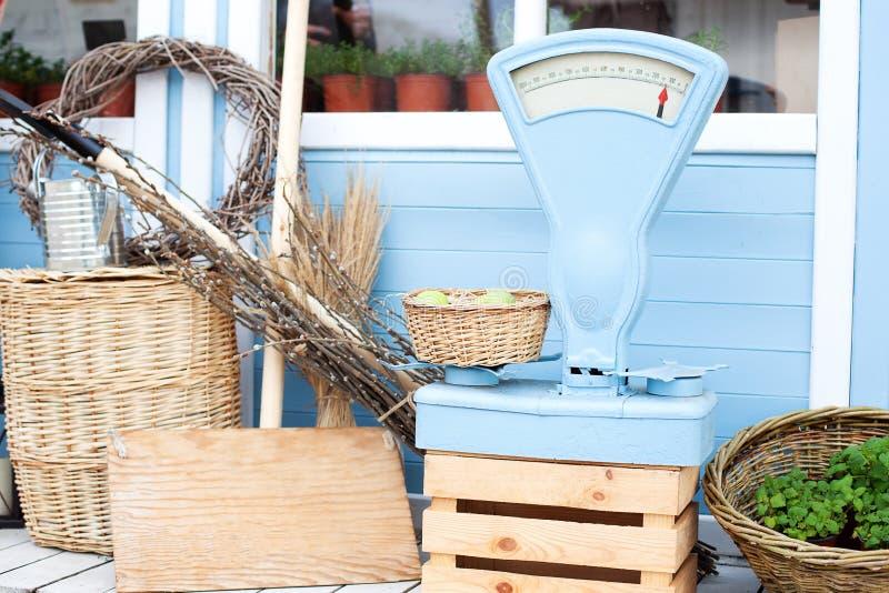 在园艺设备旁边的柳条筐对一栋蓝色乡间别墅的墙壁 夏天季节性假期 p的庭园花木 免版税库存图片