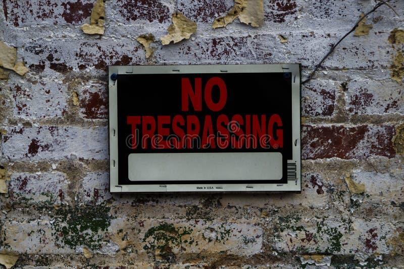 在困厄的砖墙上的没有侵入的标志 库存图片
