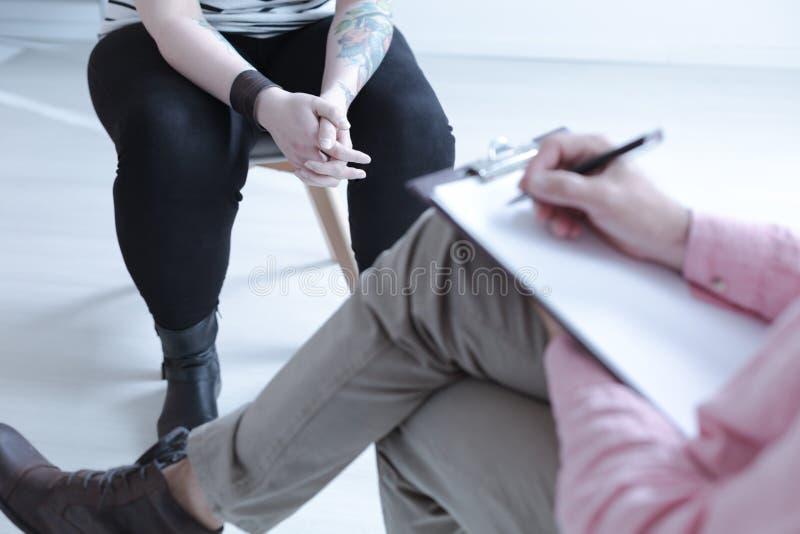 在困难的少年的特写镜头有在疗法期间的纹身花刺的与c 免版税库存照片