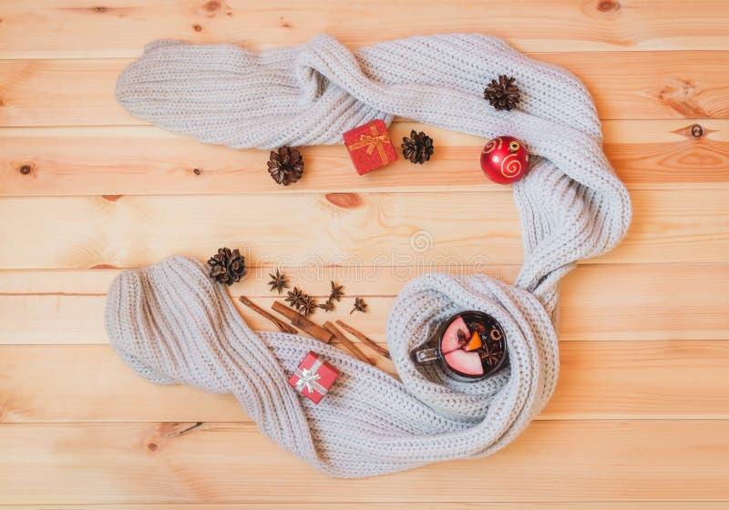 在围巾、圣诞节球、礼物和香料包裹的杯加香料的热葡萄酒 库存照片