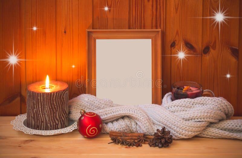 在围巾、木制框架、圣诞节球、蜡烛和香料包裹的杯加香料的热葡萄酒 免版税库存照片