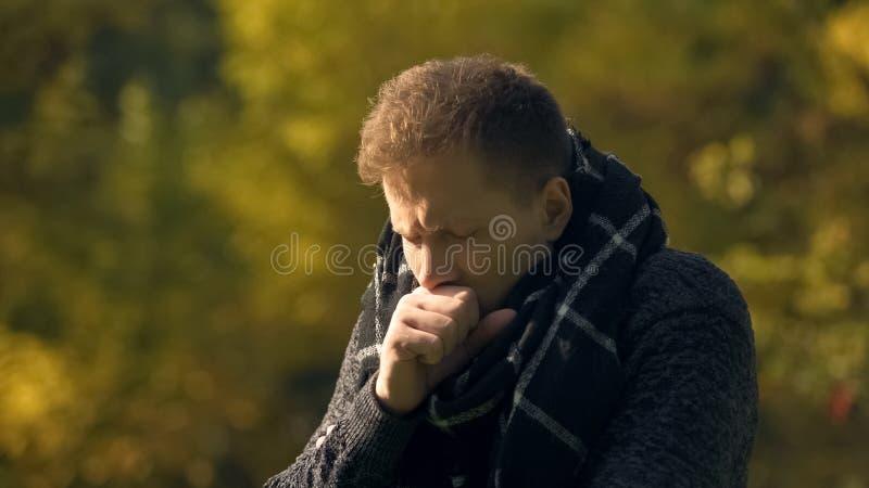 在围巾的病的男性咳嗽在公园,感冒,肺炎风险,传染的 库存图片