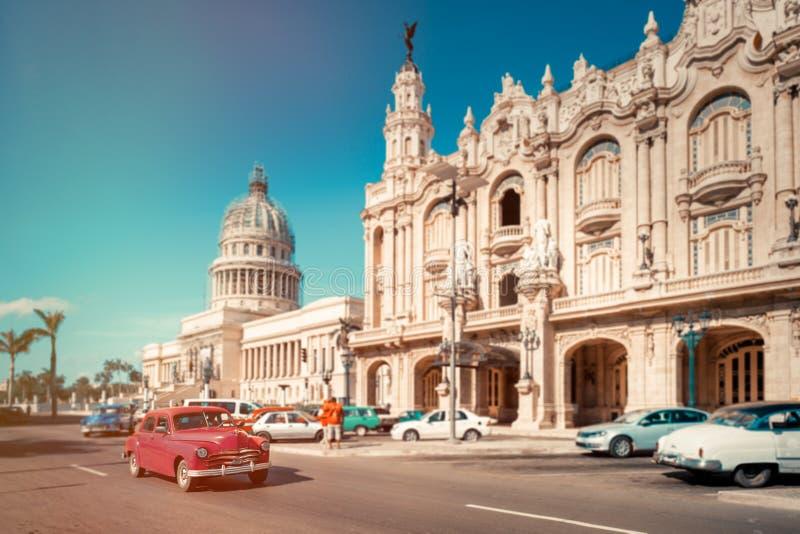 在国会大厦和哈瓦那旁边盛大剧院的古董车  库存图片