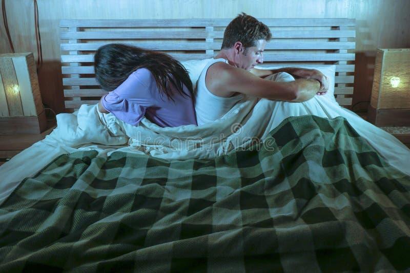 在国内战斗以后的哀伤的夫妇与沮丧妇女哭泣和沮丧的男朋友坐床不快乐在关系重音 免版税库存照片