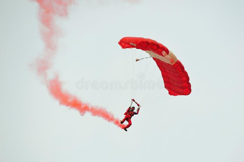 在国庆节游行(NDP)排练期间的红色狮子尽量延缓张伞的跳伞运动2013年 库存图片
