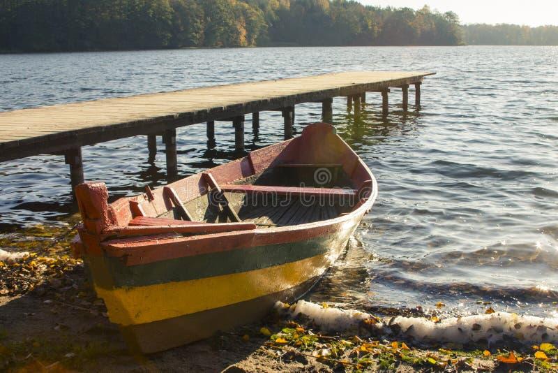 在国旗的颜色绘的木小船在湖的岸的在特拉凯 r 免版税图库摄影