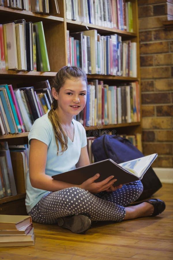 在图书馆地板上的小女孩读书在小学 照片拍摄时间: november 09th