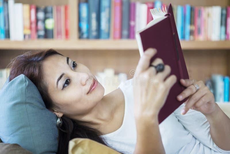 在图书馆的有吸引力的女性阅读书 库存照片