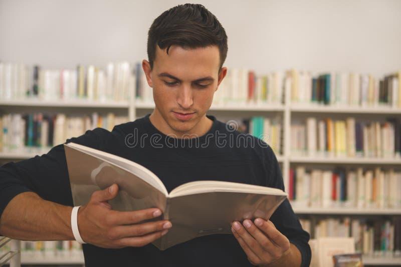 在图书馆的英俊的年轻人读书 免版税库存图片