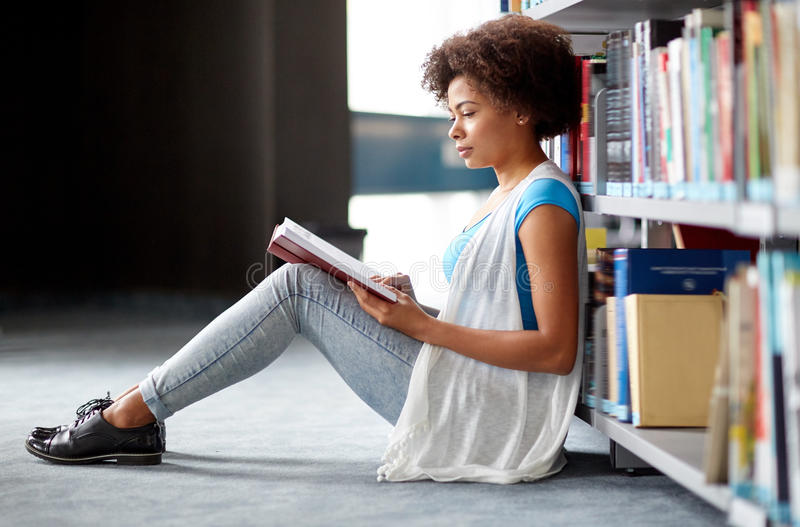在图书馆的非洲学生女孩阅读书 库存照片