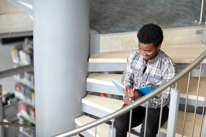 在图书馆的非洲学生男孩或人阅读书 库存照片
