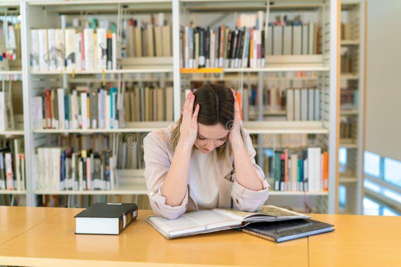 在图书馆里用尽的美丽的白种人少女 免版税库存图片