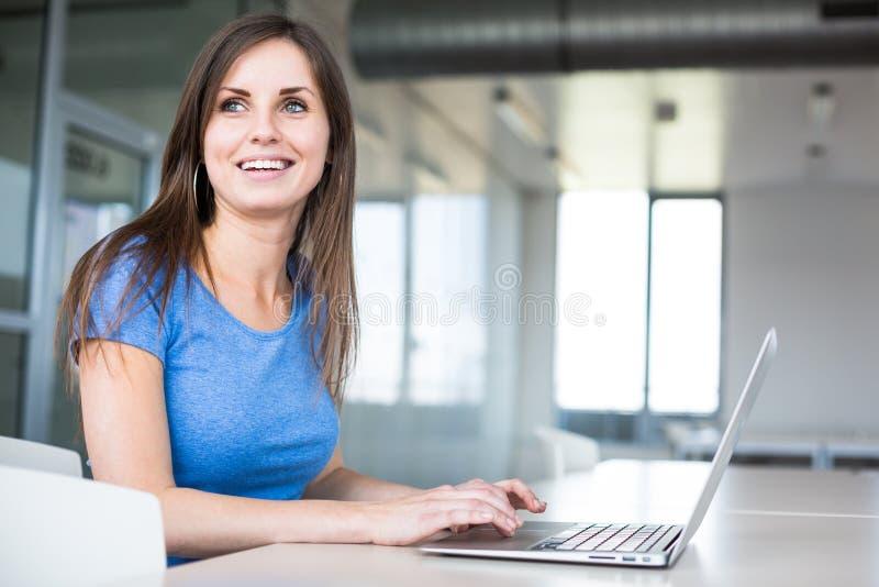 在图书馆-有膝上型计算机和书的俏丽的女学生里 免版税库存图片