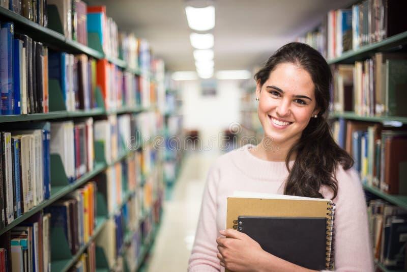 在图书馆-相当有运作在h的书的女学生里 免版税图库摄影