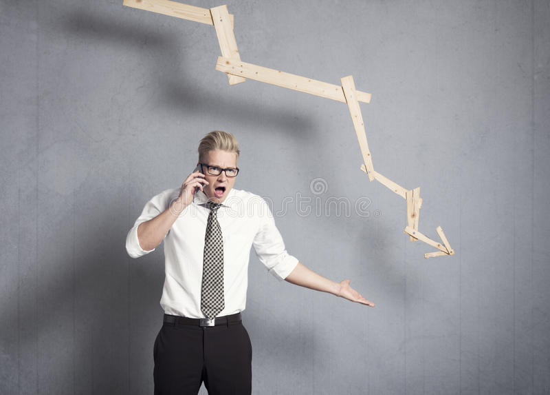在图形前面的指向恼怒的生意人下来。 免版税库存图片