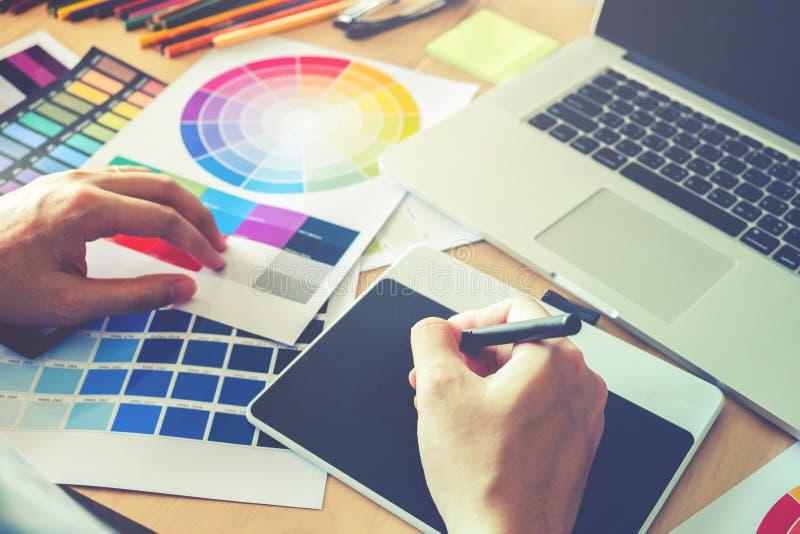 在图形输入板的图表设计师图画在工作场所 免版税库存照片