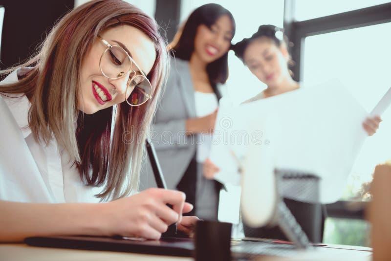 在图形输入板的年轻设计师图画,当她同事看时 免版税库存照片