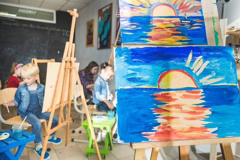 在图画班的木画架与孩子图画  前景调色板 艺术课 库存图片