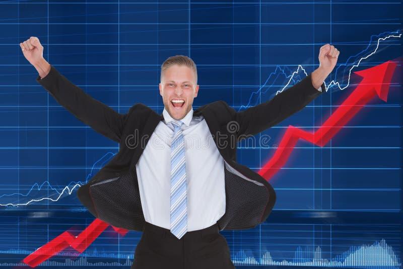 在图表前面的愉快的商人 免版税库存照片