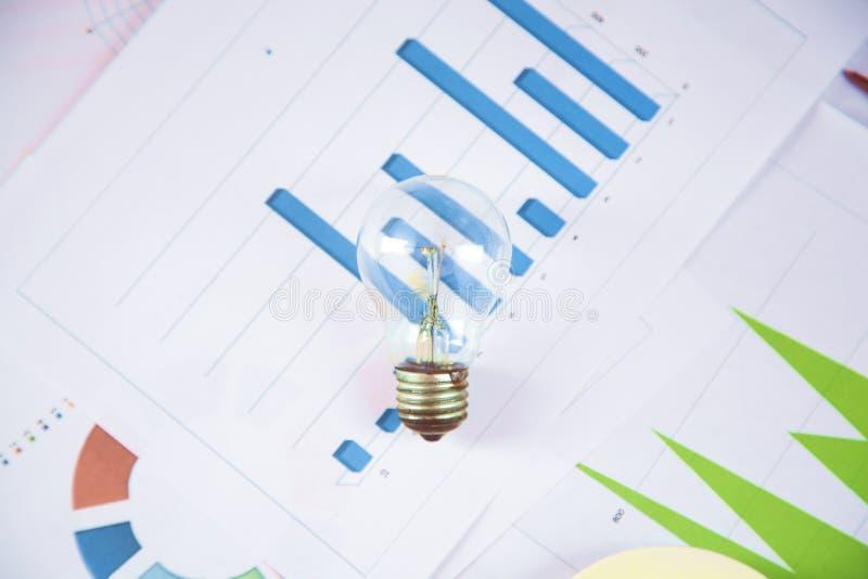 在图表的电灯泡在书桌上 库存照片
