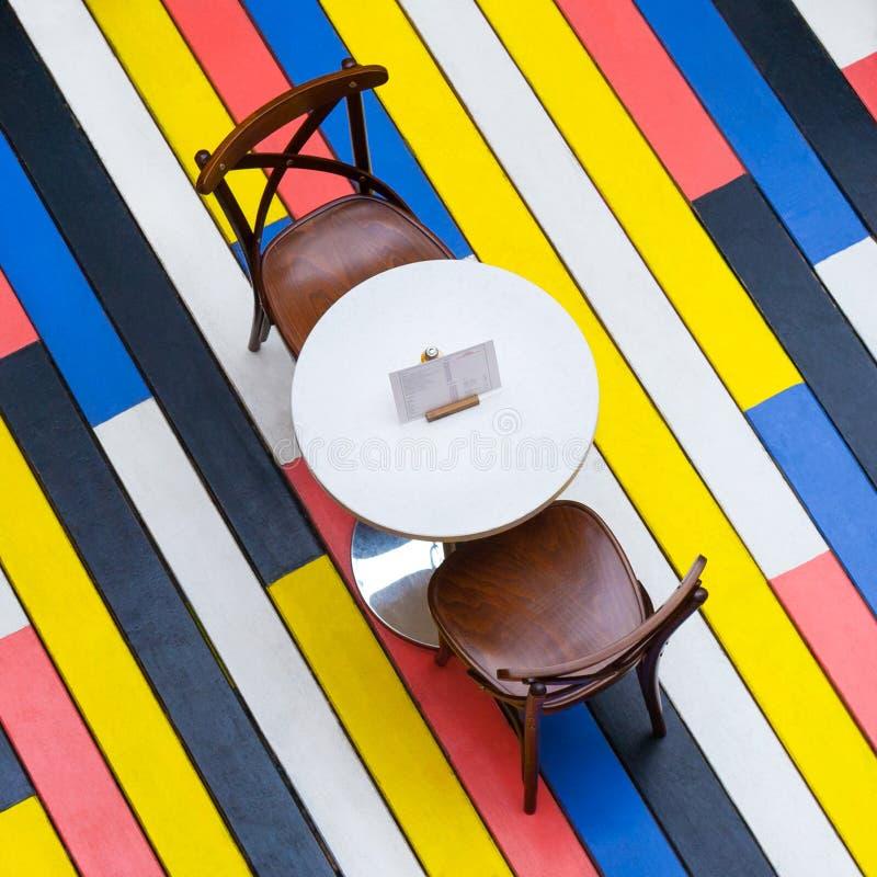在圆桌和椅子上的看法在咖啡馆方形的长宽比的一个多彩多姿的木地板上 免版税图库摄影