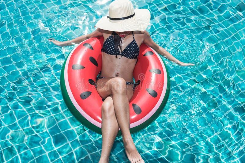 在圆环浮游物可膨胀的西瓜的妇女比基尼泳装 免版税库存照片