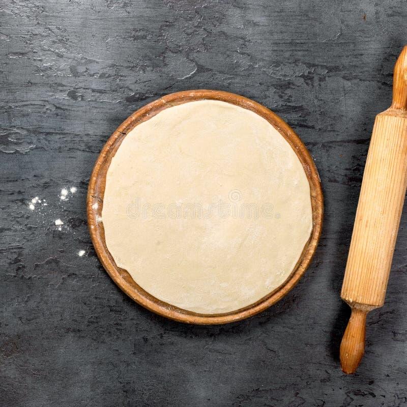 在圆的木板的薄饼面团有滚针的 免版税库存图片