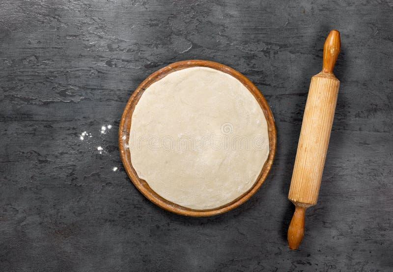 在圆的木板的薄饼面团有滚针的 免版税库存照片