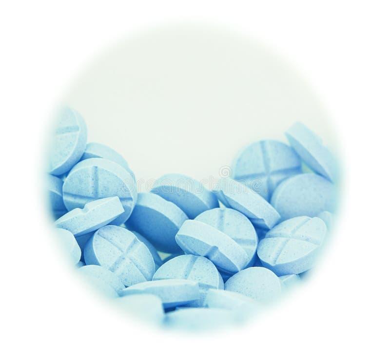 在圆的箱子的浅兰的药片在被隔绝的白色背景 库存照片