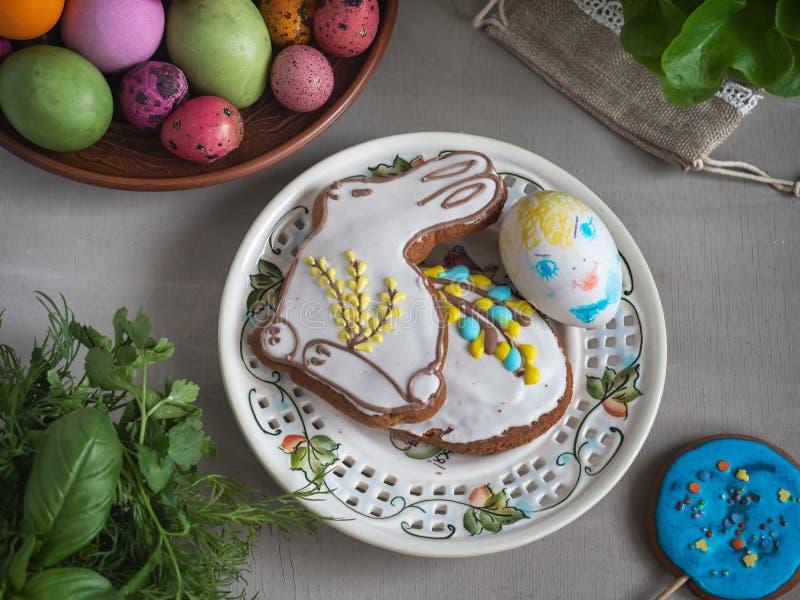 在圆的陶瓷板材的复活节款待用五颜六色的鸡蛋和姜饼在轻的背景,新绿色,采取从关闭 免版税图库摄影