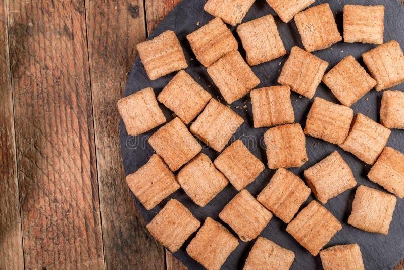 在圆的页岩板的酥脆方形的麦子枕头在老木桌上 免版税库存图片